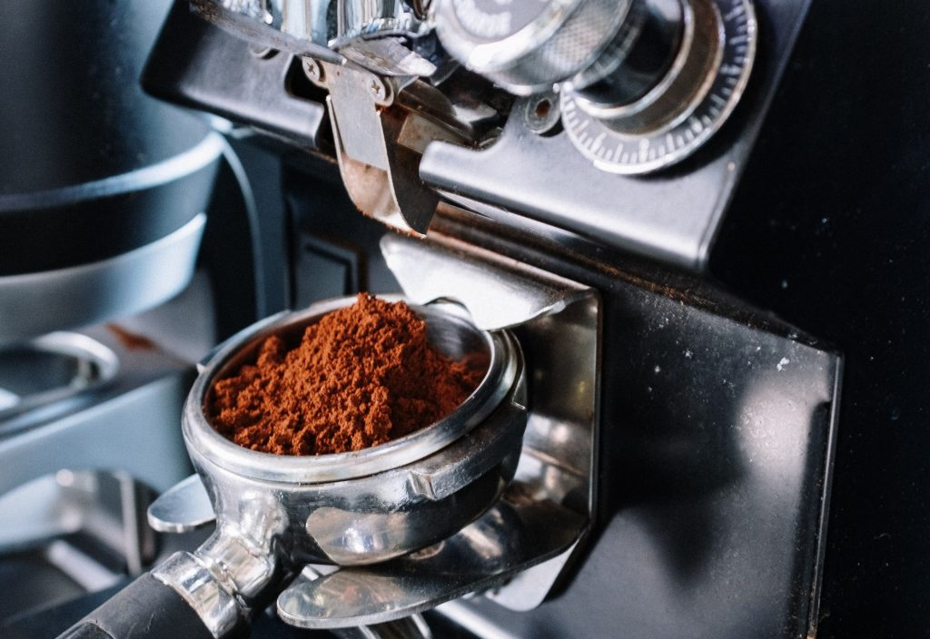 A Mythos One grinder grinding coffee beans into a portfilter