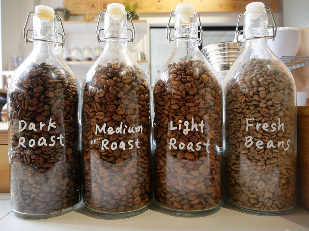 bottles of coffee beans side by side, with different roast levels